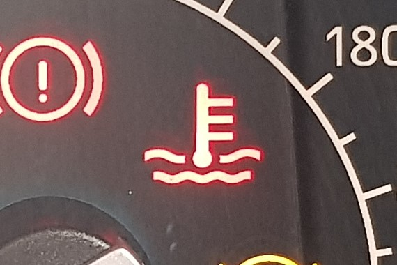 Warning light that looks like a thermometer coming out of some waves.